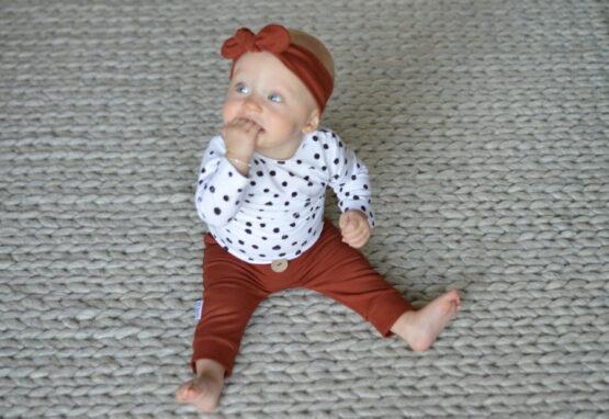 baby met roestbruin haarbandje en broekje uit herfstcollectie