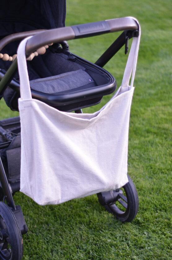 kinderwagentas hangend aan de duwstang van de kinderwagen